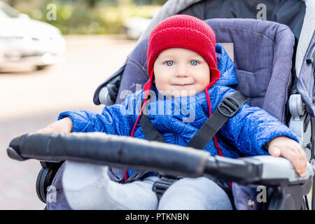 Cute little baby boy sitting in stroller and smiling during walk on cold autumn or winter day.Adorable kid wearing blue jacket and knitted red hat out - Stock Photo