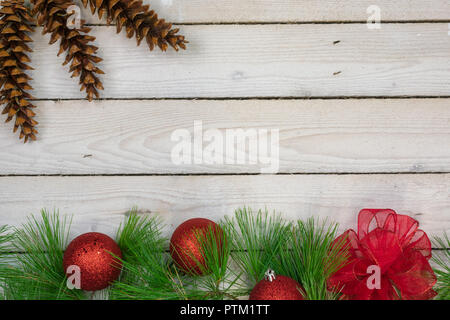 A border of white pine boughs , three red ornaments, and a red bow along the bottom with three white pine cones in the upper left corner - Stock Photo