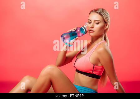 attractive sportswoman drinking water from sport bottle on red - Stock Photo