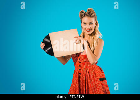 portrait of young pin up woman in stylish vintage dress with vinyl record on blue backdrop - Stock Photo
