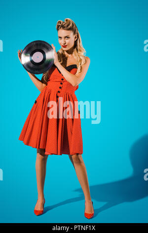 young pin up woman in stylish vintage dress with vinyl record on blue backdrop - Stock Photo