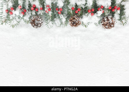 Snow covered Christmas Background with natural fir tree twigs, pine cones and red berries. Top view. - Stock Photo