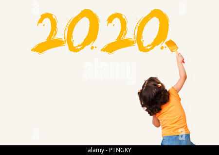 Cute little girl drawing new year 2020 with painting brush on wall background - Stock Photo