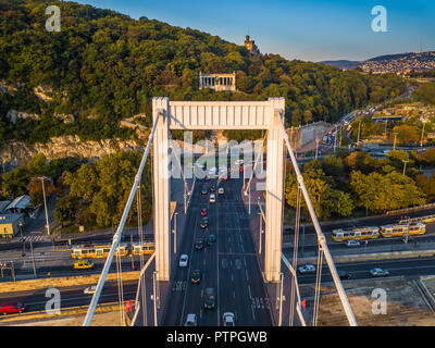 Budapest, Hungary - Aerial view of Elisabeth bridge (Erzsebet hid) and Gellert Hill at sunrise with heavy traffic and traditional yellow trams - Stock Photo