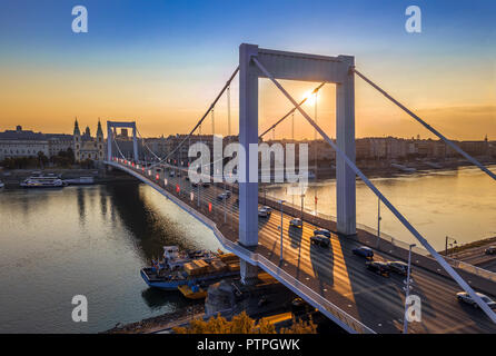 Budapest, Hungary - Beautiful Elisabeth Bridge (Erzsebet hid) at sunrise with golden and blue sky, heavy morning traffic and traditional yellow tram a - Stock Photo