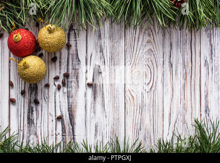 three New Year's ball toys with pine nuts on a white wooden background, sosonic branches, copy space - Stock Photo