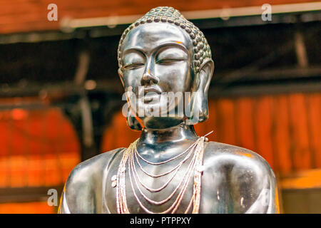 Buddha statue used as a necklace holder stand on display at Camden Market in London - Stock Photo