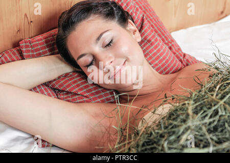 Junge Frau entspannt sich im Heubett eines Wellnesshotels Young woman relaxing in a bed of hay in spa hotel women, young, lie, sleep, bed, in, hay, ar - Stock Photo