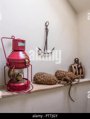 Red oil lamp with rope buoys, winch and anchor - Stock Photo
