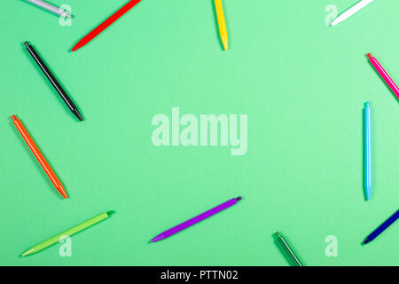 Colorful pens frame on green background - Stock Photo