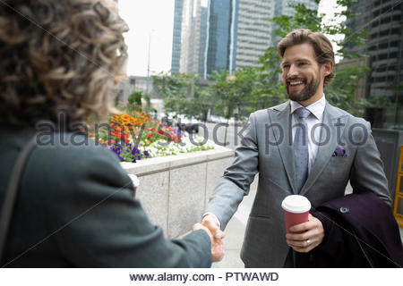 Businessman with coffee shaking hands with businesswoman on city sidewalk - Stock Photo