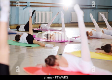 The training of young dancers in the ballet studio. Young dancers perform gymnastic exercises during a warm-up in the classroom. Sport, gymnastics, ch - Stock Photo