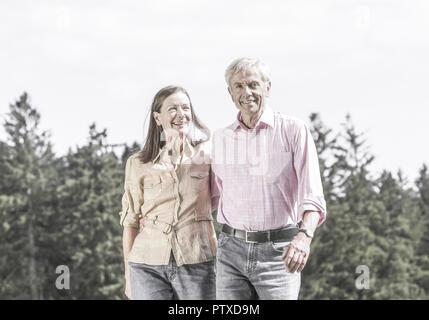 Seniorenpaar beim Spazierengehen an Waldrand (model-released) - Stock Photo
