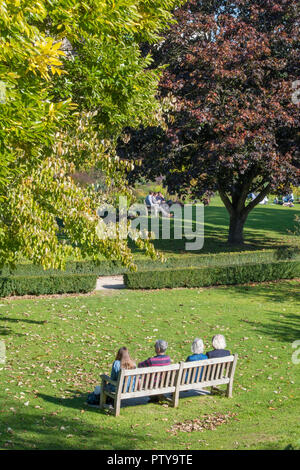 4 people or a group of older middle aged ladies and gentlemen sitting on a wooden park pench in bishop's garden at chichester cathedral in the autumn. - Stock Photo
