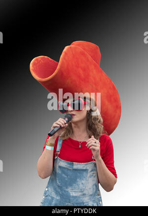 Portrait of a pretty female singer holding a microphone and wearing a giant red hat and huge red sunglasses - Stock Photo