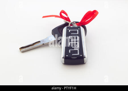 Car keys with red ribbon on white background - Stock Photo