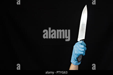 Hand of a girl in a blue medical glove with a knife on a black background, close-up - Stock Photo
