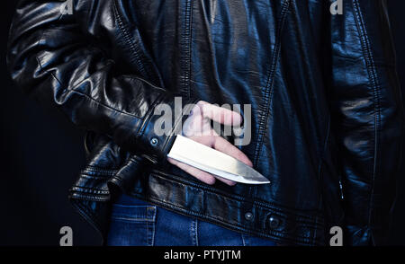 A man in a leather jacket holds a knife behind his back, a black background - Stock Photo