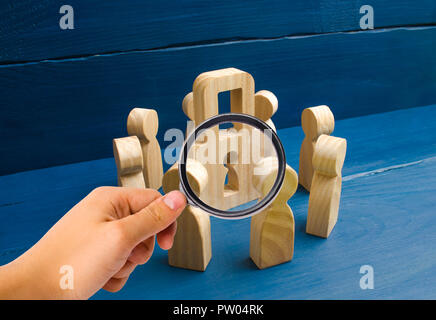 Bank secrecy, medical secret. Magnifying glass is looking at the Wooden figures of people standing around a padlock on a blue background. the protecti - Stock Photo