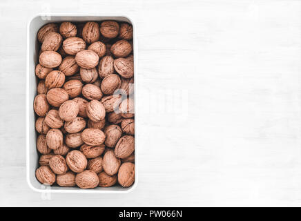 Box full of walnuts, on white painted wooden background with copy space. - Stock Photo