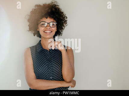 Portrait of beautiful young woman in casuals standing by a wall and smiling. Happy young african female with curly hair wearing spectacles looking at  - Stock Photo