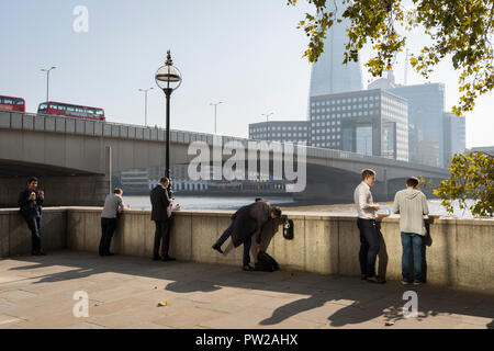 Londoners and office workers in the City of London - the capital's financial district - enjoy late summer temperatures on Fishmongers Hall Wharf overlooking the Shard skyscraper, London Bridge and the Thames river, on 10th October 2018, in London, England. - Stock Photo
