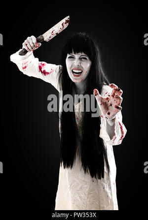 Halloween horror. Crazy bloody scary zombie girl holding knife butcher cleaver looks into camera on black background - Stock Photo
