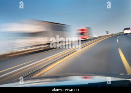 Blurred motion of vehicles moving on road seen through car windshield - Stock Photo