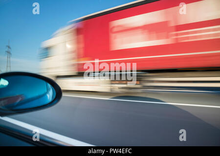 Blurred motion of truck moving on road seen through car window - Stock Photo