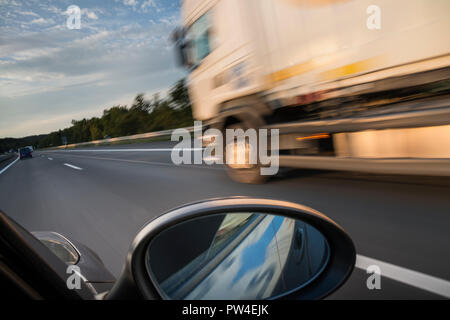 Blurred motion of truck moving on road against sky seen through car window - Stock Photo