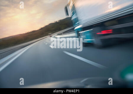 Blurred motion of truck moving on road seen through car windshield during sunset - Stock Photo
