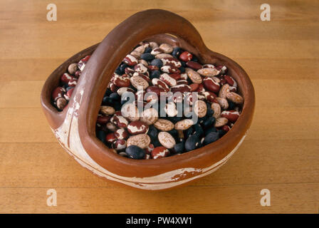 Dried beans: Anasazi beans, pinto beans, and black beans in a Pueblo pottery bowl, New Mexico. Photograph - Stock Photo
