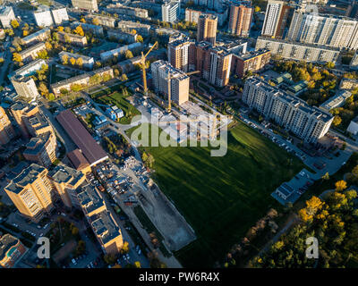 Aerial view of the construction site of a building in the industrial center of the city among buildings located close to each other with three yellow  - Stock Photo