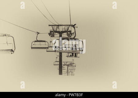 A lonely snowboarder sitting completely alone in a chairlift. Freezing cold foggy weather is making this ride extremely uncomfortable. Taken in Tignes - Stock Photo