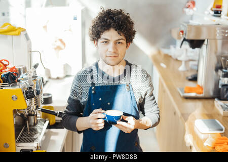 Barista holding coffee cup near bar counter in bright modern cafe. - Stock Photo