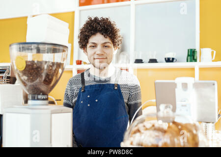 Friendly hospitable barista smiling and standing behind bar counter. - Stock Photo