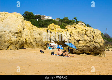 29 September 2018 A couple sit in the sun beside a small sun brolly on a remote part of the Oura Praia beach in Albferiah on the Algarve in Portugal - Stock Photo