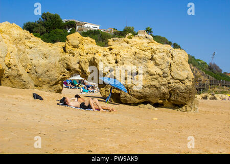 29 September 2018 A couple sit in the shade of a sun brolly on a remote part of the Oura Praia beach in Albferiah on the Algarve in Portugal - Stock Photo