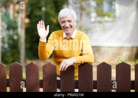 Cheerful senior man in casualwear standing by wooden fence and waving his hand to you - Stock Photo