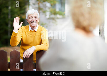 Cheerful and friendly mature man waving hand to his neighbour while standing by fence - Stock Photo