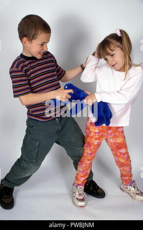 brother & sister fighting over a toy - Stock Photo