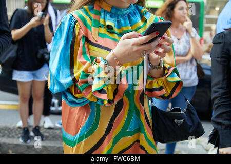 MILAN, ITALY - SEPTEMBER 20, 2018: Woman with yellow, orange, blue and green dress and Prada bag before Max Mara fashion show, Milan Fashion Week stre - Stock Photo