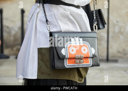 MILAN, ITALY - SEPTEMBER 20, 2018: Woman with black leather Prada bag with orange robot design before Max Mara fashion show, Milan Fashion Week street - Stock Photo