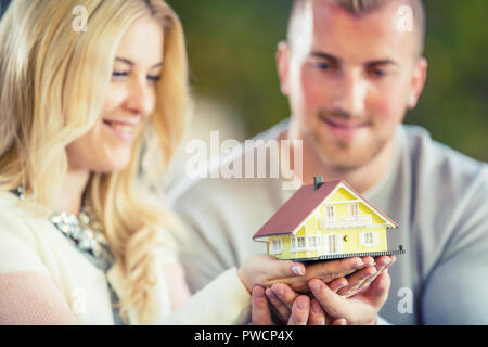 Young loving couple holding small model house. - Stock Photo