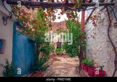 beautiful view of scenic narrow alley with  traditional houses colorful flowers and cobbled street  in a village of crete. - Stock Photo
