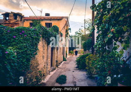 beautiful view in vintage style of narrow alley with  old house, colorful flowers  and a traditional elderly woman dressed in black in a village in cr - Stock Photo