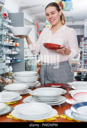 Young woman customer choosing dishes in the tableware store indoor - Stock Photo