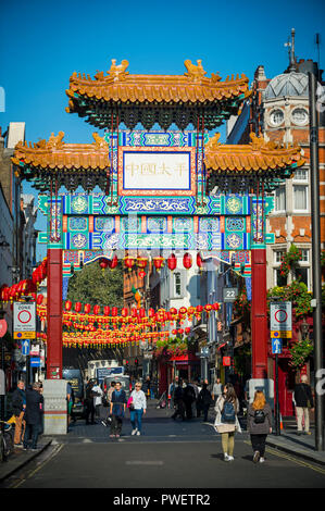 LONDON - OCTOBER 10, 2018: Decorative red lanterns hang above the street beyond a decorative gate erected in 2016 to mark the entrance to Chinatown. - Stock Photo