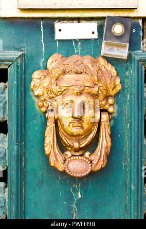 Old rusty  vintage door knocker with a face on a green wooden door with chipped paint. - Stock Photo