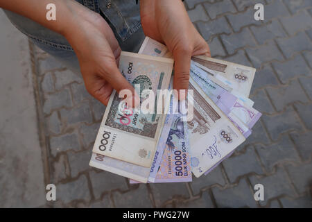 A woman counting Uzbek soʻm banknotes in the street, Uzbekistan - Stock Photo